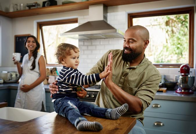 Shot of a young man giving his adorable child a high five at home.
