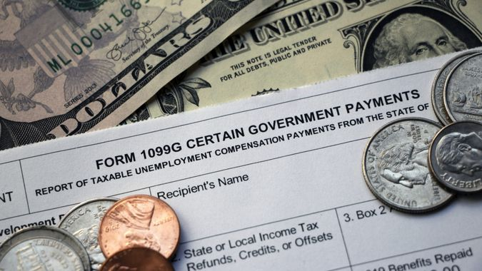 Closeup of the top of a tax Form 1099G Certain Government Payments - Taxable Unemployment Compensation Payments on top of cash with some coins scattered on top.