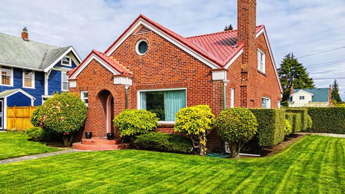 Photo of a small American red brick home on a sunny day.