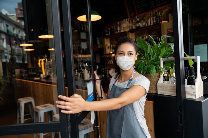 Happy business owner opening the door at a cafe wearing a facemask to avoid the spread of coronavirus – reopening after COVID-19 concepts.