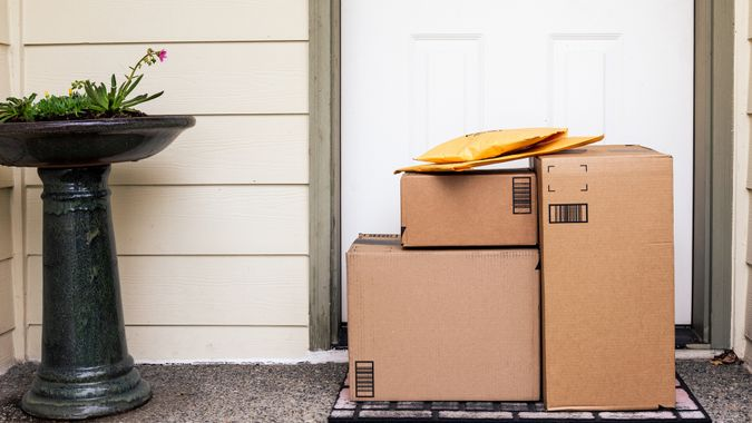 Front Door of House with Stack of Delivery Boxes from Online Ordering and E-commerce.