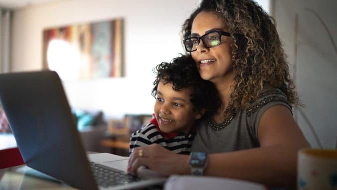 Mature woman working at home, carrying young son.