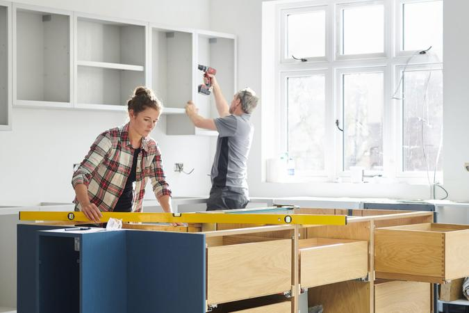 a female kitchen fitting cupboards for worktop.