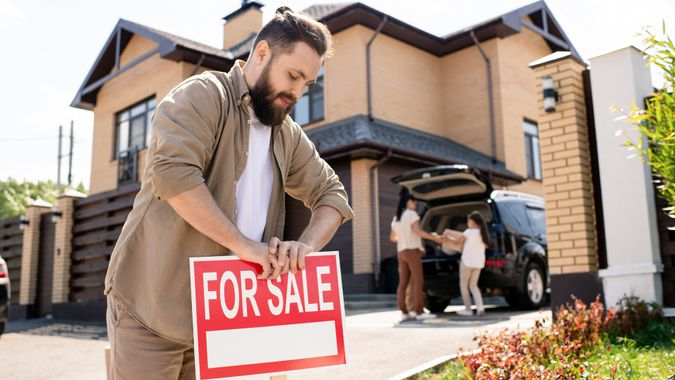 Young bearded father placing For sale sign into ground near house while putting house up for sale.
