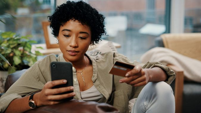 Shot of a young woman holding her credit card while using her cellphone at home.