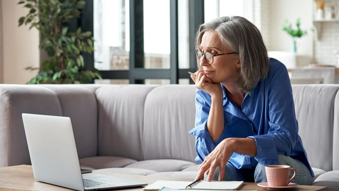 Senior mature older woman watching business training, online webinar on laptop computer remote working or social distance learning from home.