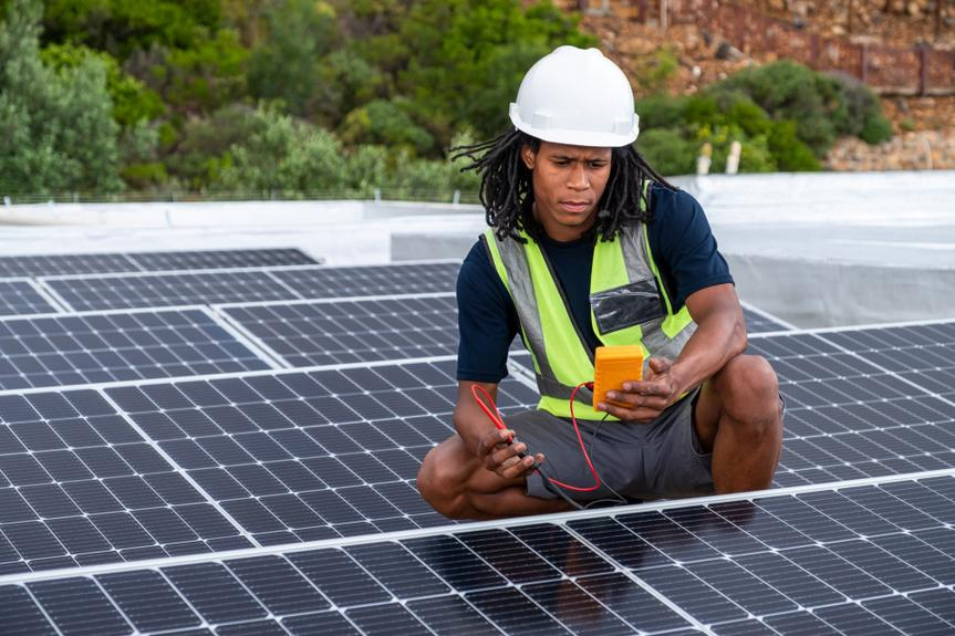 An African man with protective gear checks the voltage of the solar panels that he has just installed on a roof.
