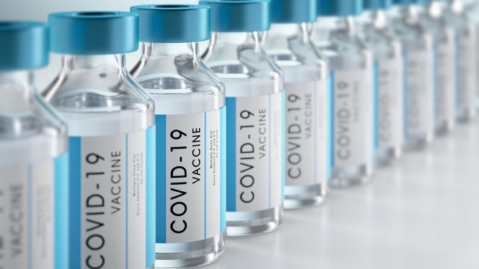 Row Covid-19 or Coronavirus vaccine flasks on white background.