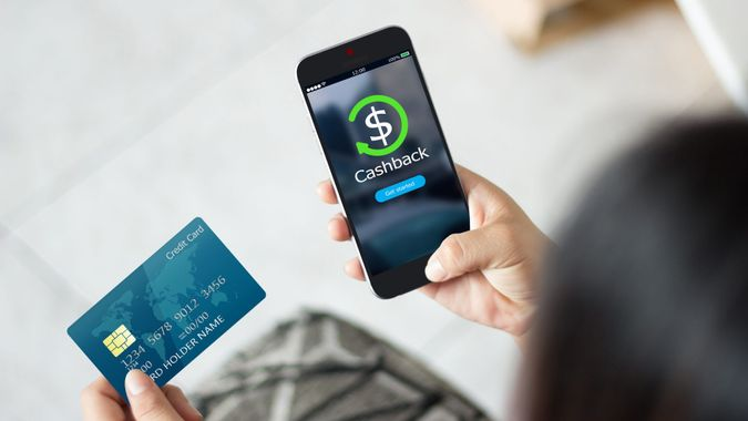 Female hands using mobile phone and holding credit card.