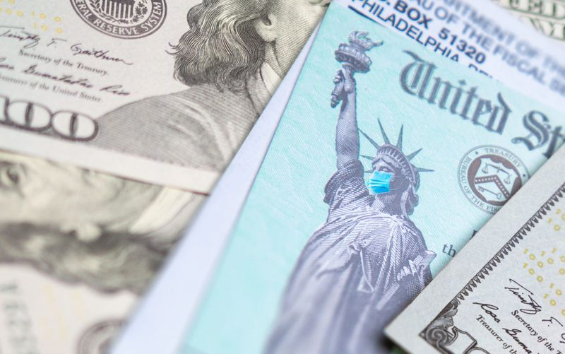 United States IRS Stimulus Check with Statue of Liberty Wearing Medical Face Mask Resting on Money.
