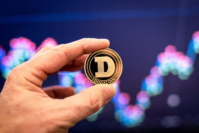 Dogecoin being held in front of chart.