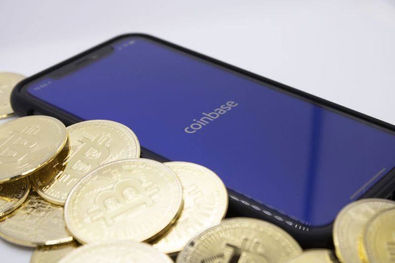 Bitcoins placed beside Coinbase App on iPhone, illustrating one of the largest Bitcoin providers, photographed in Cologne, Germany, 14th of April 2021.