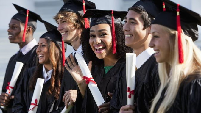 Multi-ethnic friends graduating together, in cap and gown.