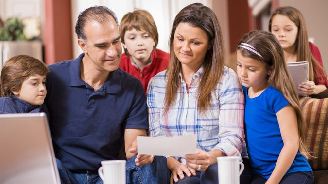 Happy family with four children discuss the family budget together as mom and dad collaborate using laptop to pay monthly bills while sitting on their living room sofa at home.