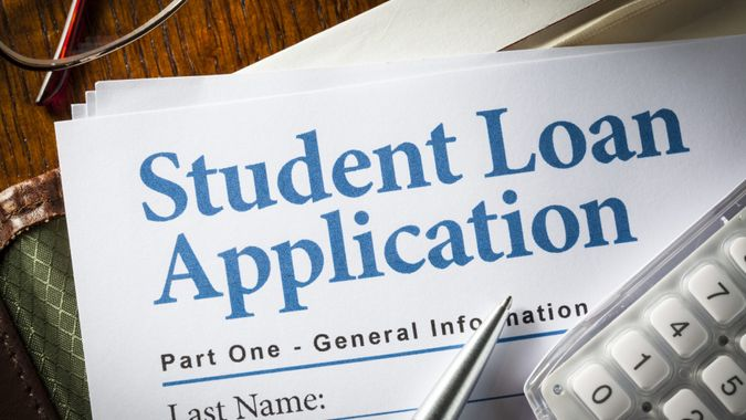 Student Loan Application with pen, calculator and glasses.