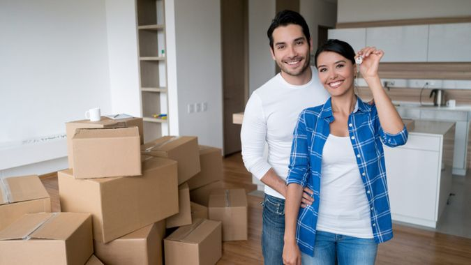 Happy young couple holding keys to their new house while moving and looking at the camera smiling.