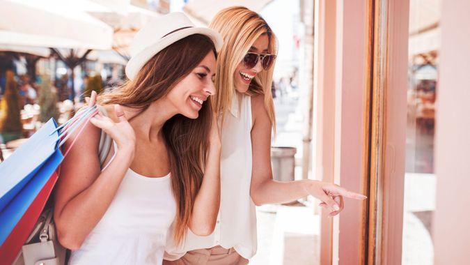 Two smiling shopaholic women enjoying in shopping, having fun together in the city.
