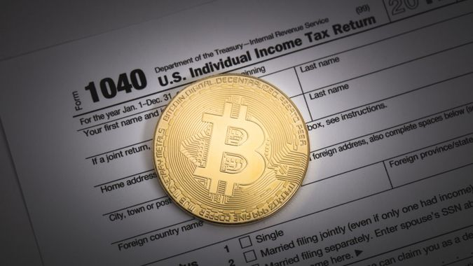 An editorial stock photo of a studio shot of a Bitcoin with some IRS 1040 tax forms.