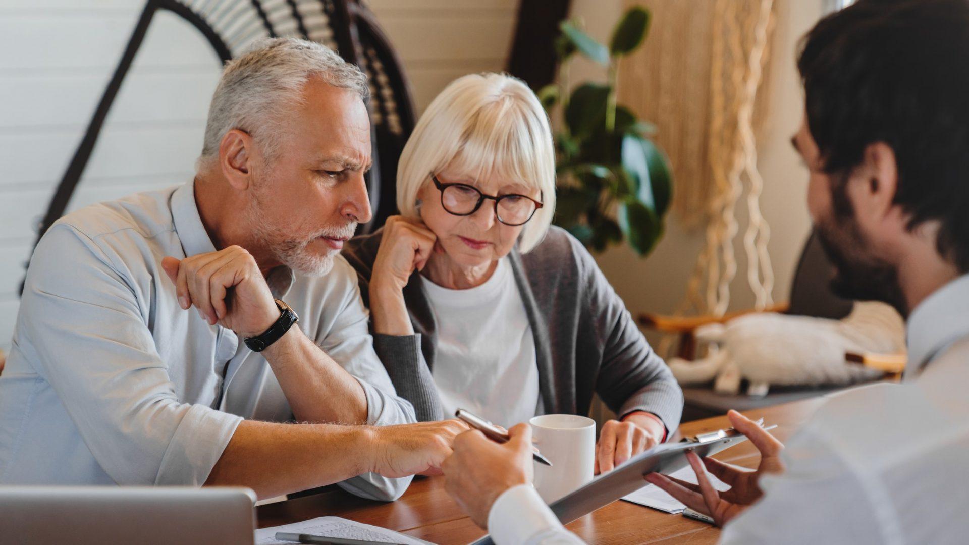 Financial advisor explaining paperwork to elderly retired couple front of desk.