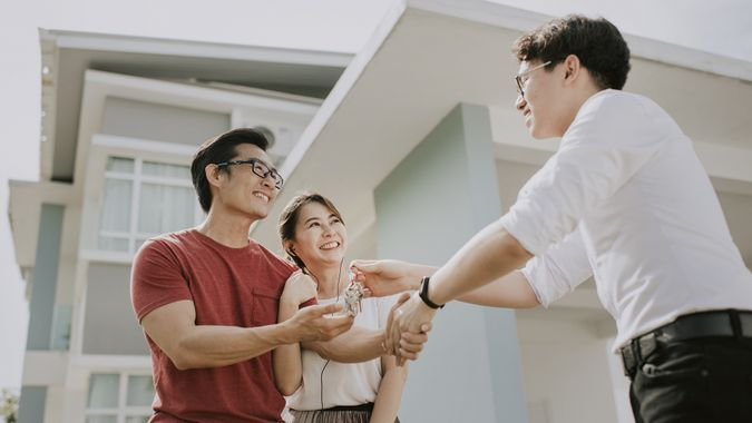 An asian chinese family moving into new house and received the house key from real estate agent stock photo