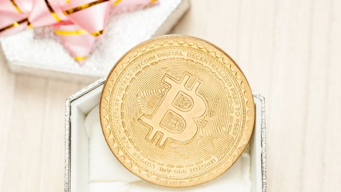 Golden virtual coin bitcoin and gift box with pink ribbon. trendy gift. stock photo