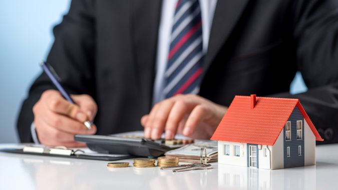 Businessman signs the contract. Purchase agreement for new house. Home ownership concept. stock photo