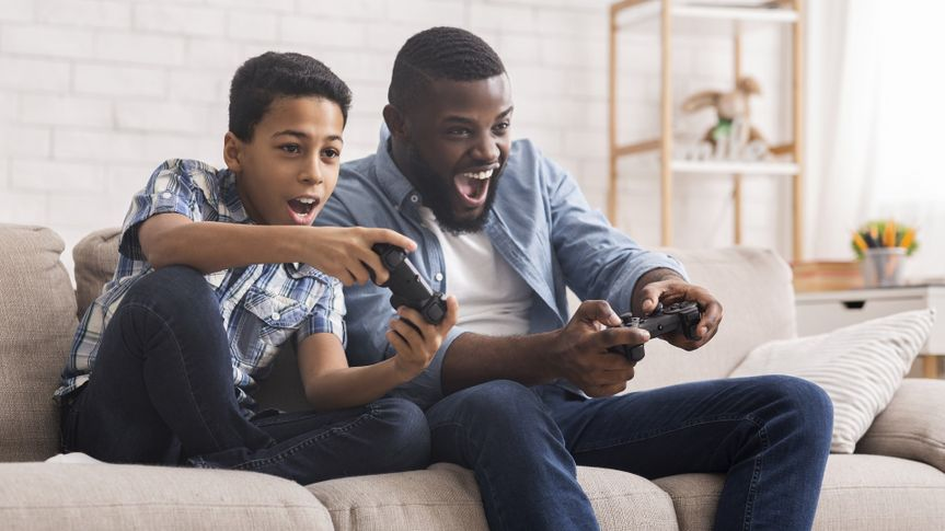 Cheerful Black Father And Son Competing In Video Games At Home stock photo