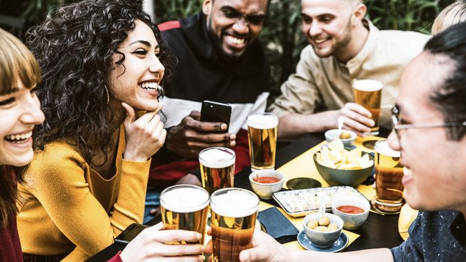 Happy diverse friends drinking beer at brewery pub - Group of young people having fun together at backyard home party - Friendship concept stock photo