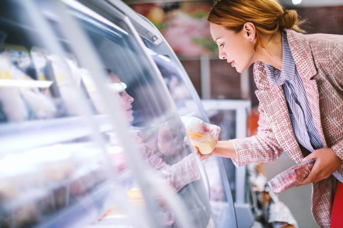 Attractive smiling brunette taking meat from a fridge at local supermarket.