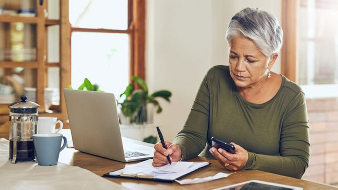 Shot of a mature woman going through paperwork at home.