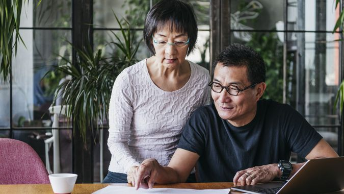 Chinese couple working on home finances with laptop, man wearing glasses and explaining, serious woman watching.