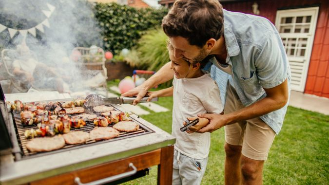Photo of father and son grilling meat during the barbecue party in their yard.