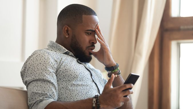 Disappointed african American millennial male sit on couch feel frustrated by unexpected bad news on cellphone, confused biracial man stressed by negative message on smartphone, cyberbullying concept.