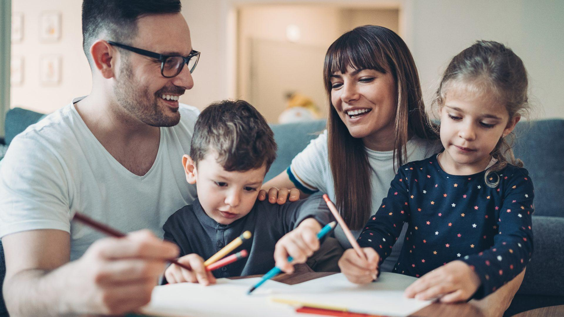 Two parents and a little boy drawing and writing together.