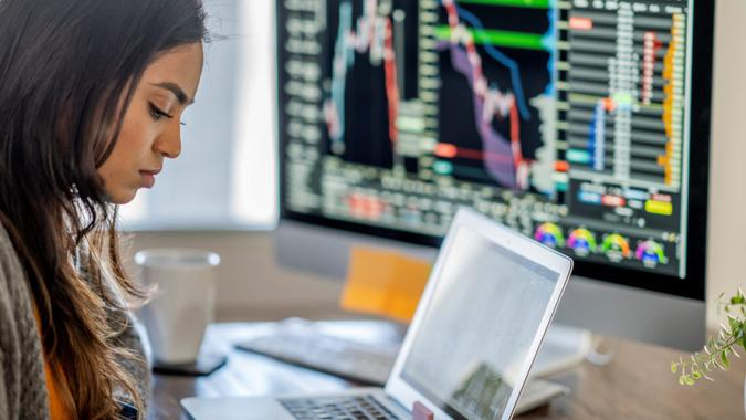 Middle Eastern woman tracking and trading stocks using laptop and desktop computer.