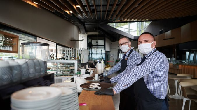 waiter in a medical protective mask serves  the coffee in restaurant durin coronavirus pandemic representing new normal concept.