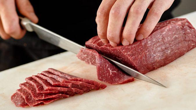 Japanese man slicing meat.