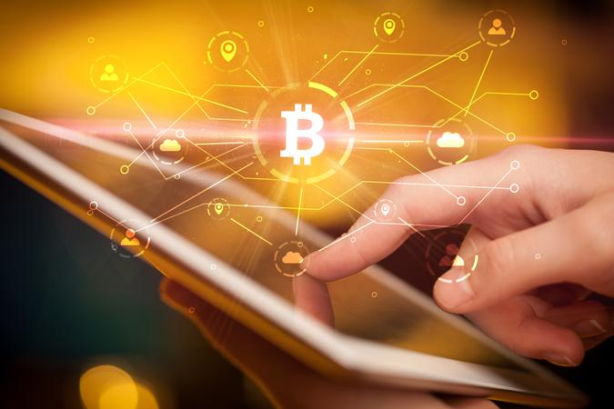 Hand using tablet with cryptocurrency bitcoin link network and online concept.