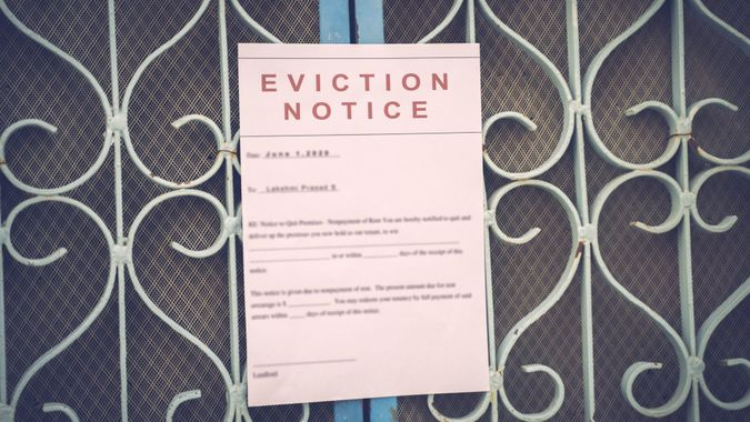 Foreclosed or eviciton notice on a main door with blurred details of a house with vintage filter.