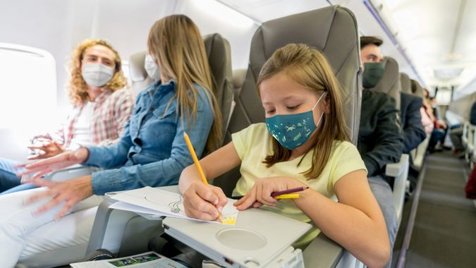 Portrait of a happy girl traveling and coloring in the plane while wearing a facemask – travel concepts.