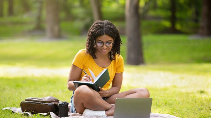 Focused millennial black girl writing something in notebook near laptop computer at park, panorama.