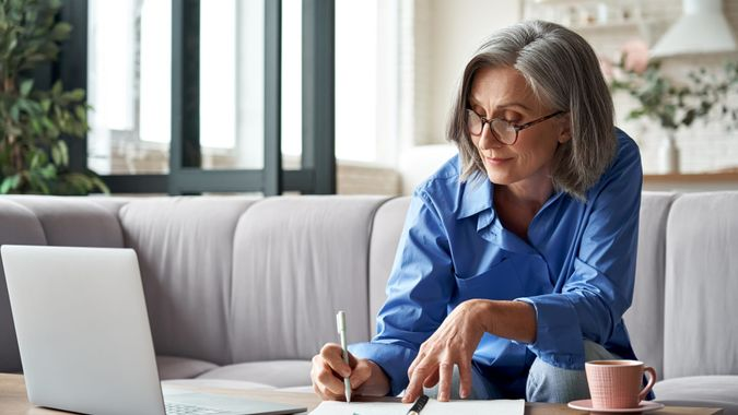 Happy stylish mature old woman remote working from home distance office on laptop taking notes.