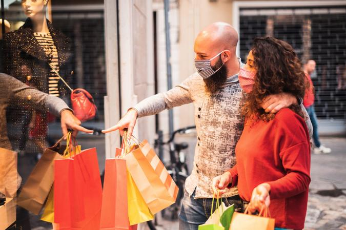 Pretty young man pointing to shop window to show clothing item his likes to his girlfriend - Beautiful young couple enjoying in shopping, having fun together, with the face mask - Consumerism, love, dating, new normal, lifestyle concept.