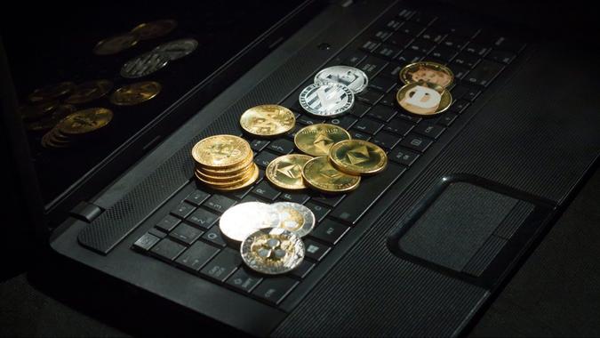 Laptop with cryptocurrencies over dark floor.