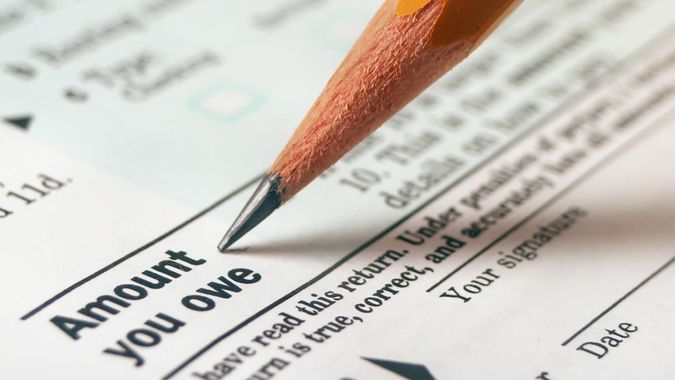 """macro of tax form with pencil pointing to """"""""amount you owe""""""""."""