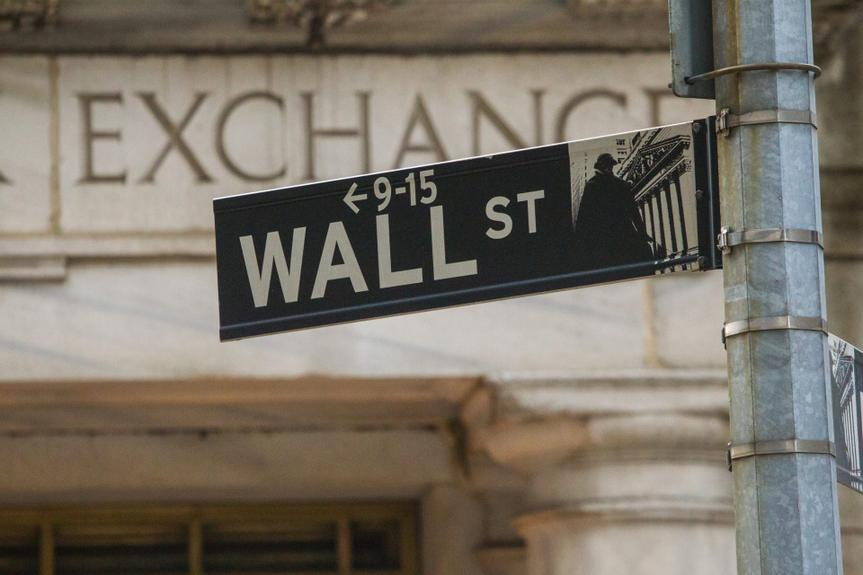The New York street sign showing Wall Street outside the New York Stock Exchange.