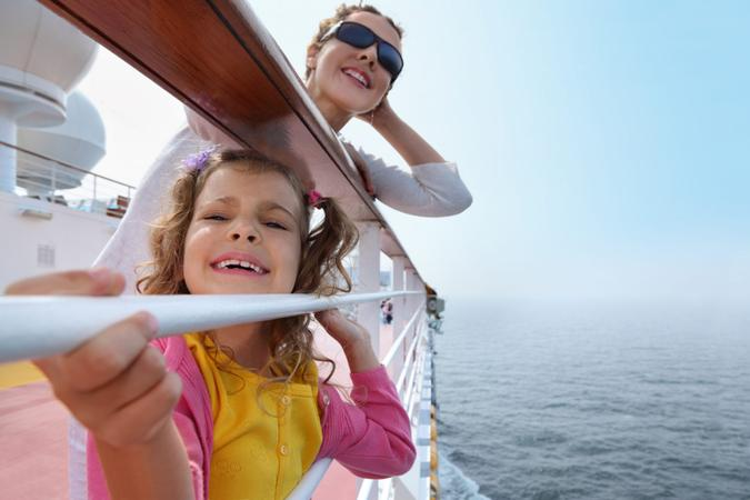 Smiling mother and daughter traveling on big cruise ship, other ship in sea.