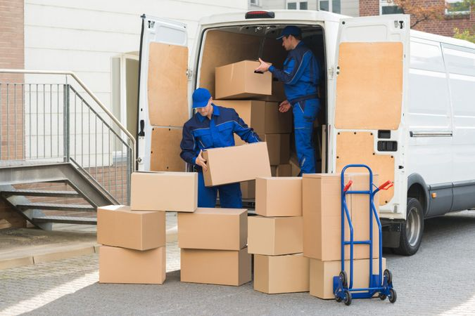 Young delivery men unloading cardboard boxes from truck on street.