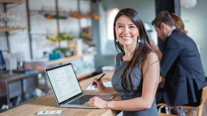 Happy business woman working at a cafe on a laptop and looking at the camera smiling.