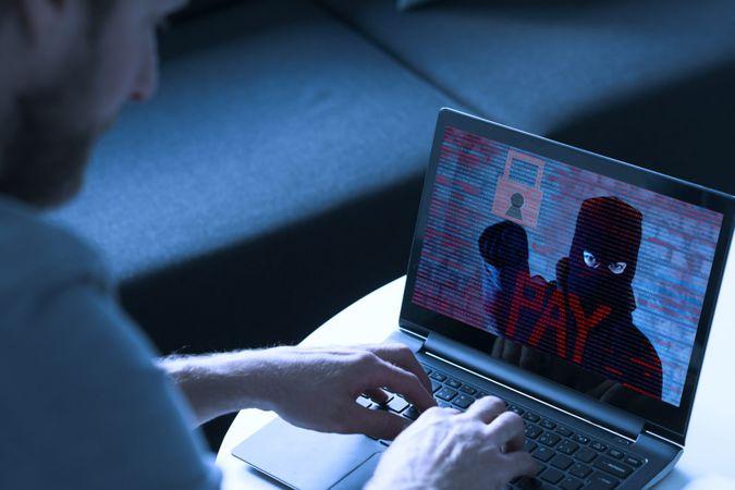 Man types on his laptop.